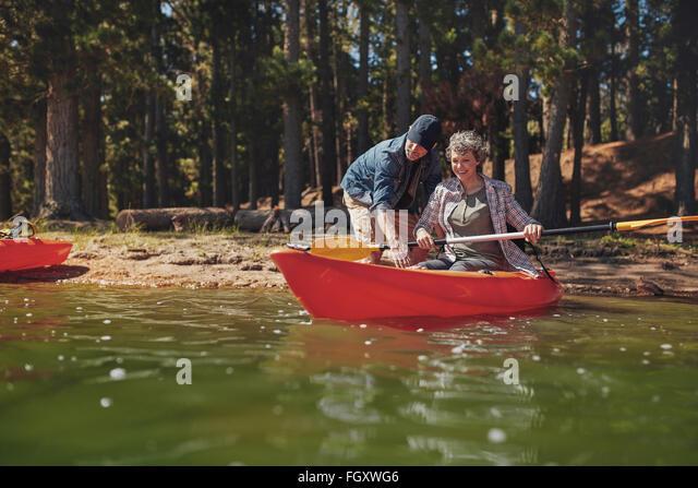 Portrait of mature woman learning to row in kayak. Man teaching kayaking to woman at the lake. - Stock Image