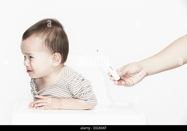 Baby boy crying, hand holding digital thermometer - Stock Image