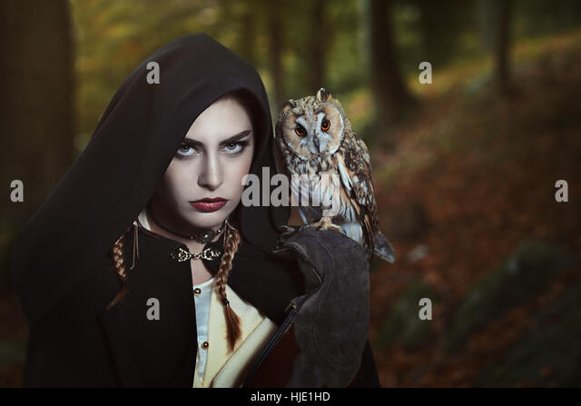 Dark hood woman with owl on her shoulder. Fantasy shot - Stock-Bilder