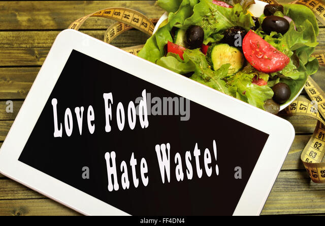 Love food Hate waste written on digital tablet - Stock Image