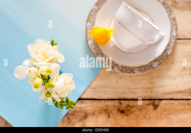 White freesias on blue mat on rustic wooden table with blurred vintage teacup and yellow freesia in background - Stock Image