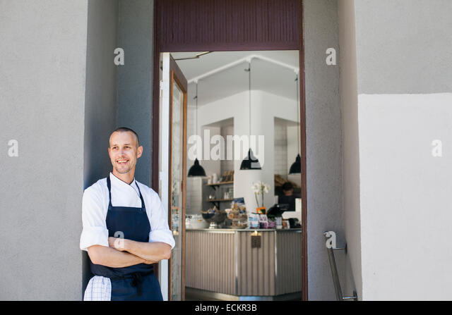 Smiling chef standing arms crossed outside commercial kitchen - Stock Image