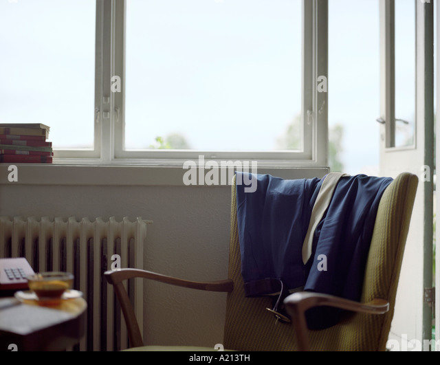 Clothes Draped on Back of Armchair - Stock Image
