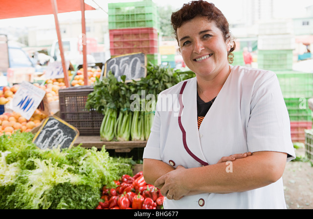 Woman trader at vegetable stall - Stock Image