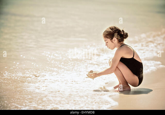 Girl playing with sand on the beach, Mexico - Stock Image