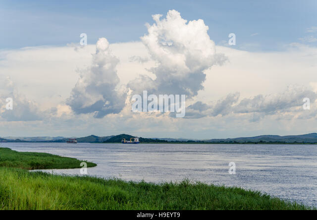 Container cargo ships on mighty Congo river with dramatic sky - Stock-Bilder