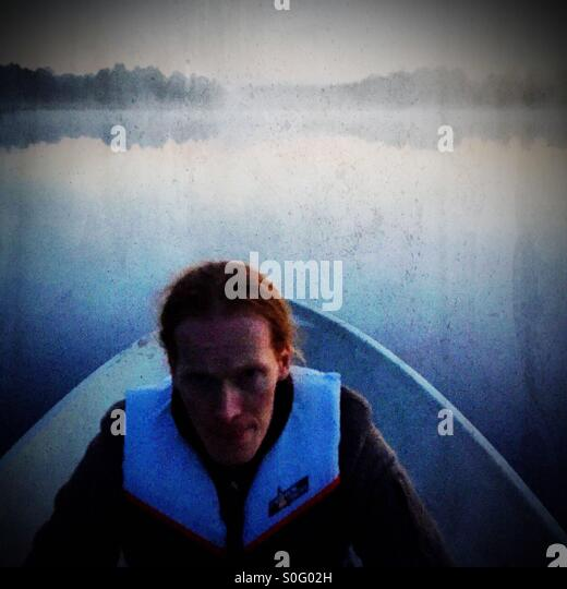 A red headed man rowing a boat - Stock Image