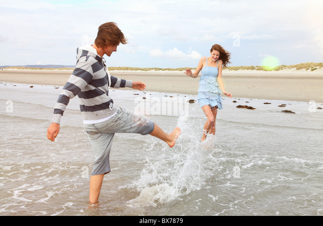 Young couple playing in the surf - Stock Image