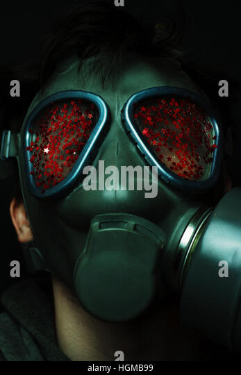 Young man with a gasmask covering by red glitter - Stock Image