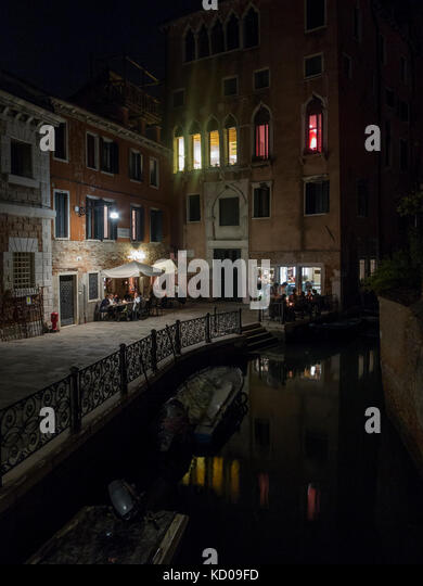 A small, quiet, romantic restaurant in Venice at night - Stock Image