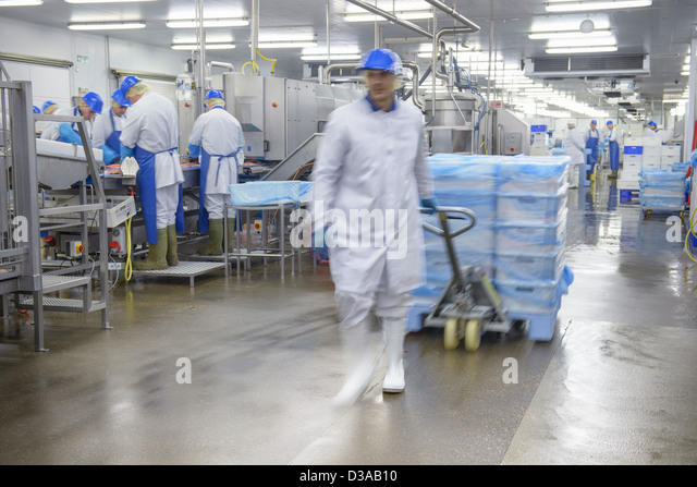 Worker pulling pallet truck through food factory, blurred motion - Stock Image