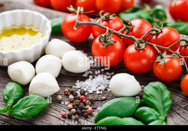 Cherry tomatoes, basil leaves, mozzarella cheese and olive oil for caprese salad - Stock Image