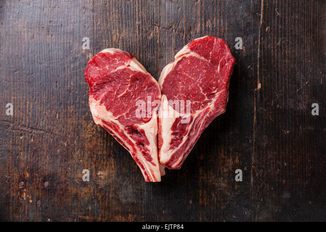 Heart shape Raw meat Ribeye steak entrecote on wooden background - Stock-Bilder