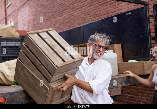 Farmers unloading crates of organic food for store - Stock Image