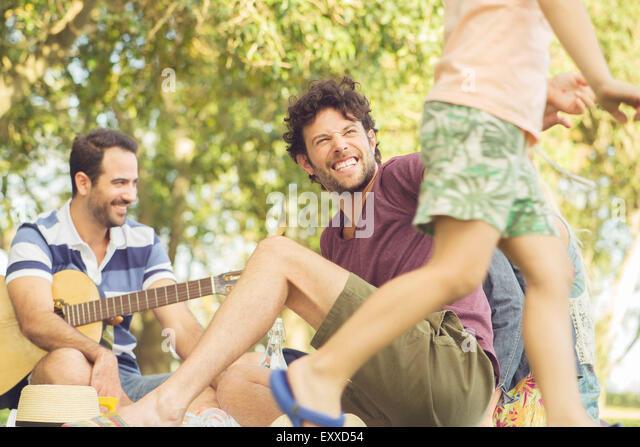 Man at picnic watching children play - Stock Image