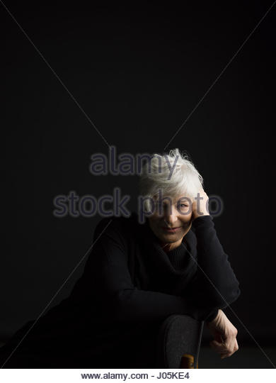 Portrait confident senior woman with white hair leaning on chair against black background - Stock Image