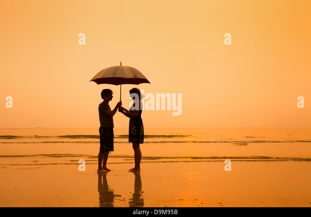 family on the beach, silhouettes of couple with umbrella - Stock-Bilder