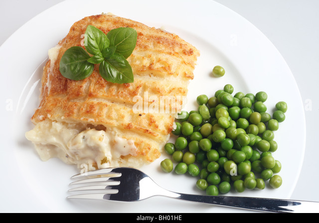 A classic fish pie made of mashed potato baked on top of bechamel sauce and cooked fish,  with green peas and basil - Stock Image