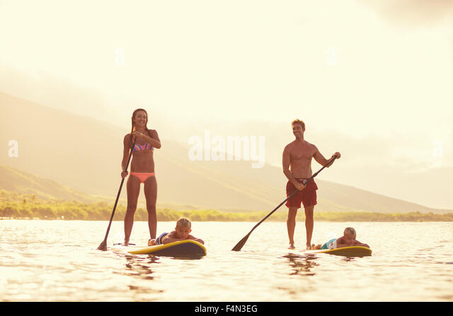 Family stand up paddling at sunrise, Summer fun outdoor lifestyle - Stock-Bilder