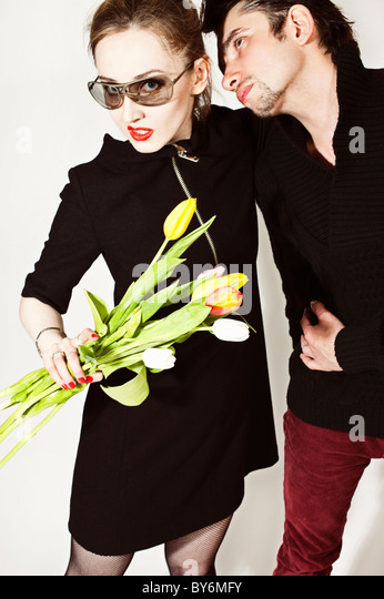 A pair of lovers with bouquet of tulips on white background - Stock Image