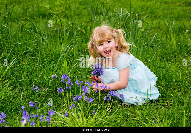UK, Warwickshire, Rugby, Happy girl (4-5) picking up bluebells on meadow - Stock Image