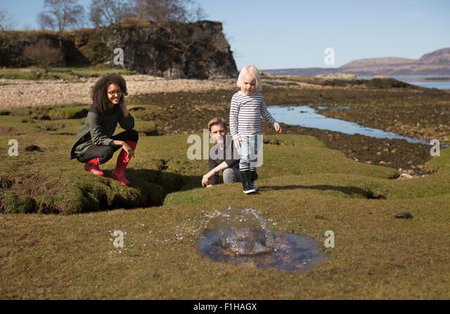 Boy throwing rock into puddle, Isle of Skye, Hebrides, Scotland - Stock Image