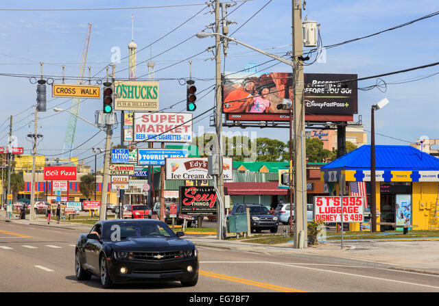 Chevrolet sports car driving on International Drive, Orlando, Florida past rows of advertising billboards, America. - Stock Image