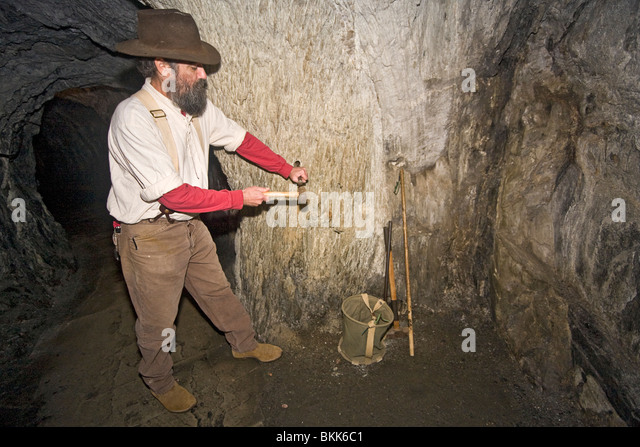 Miner drills hole for dynamite by hand to show how mining was done during gold rush days. This was known as single - Stock Image