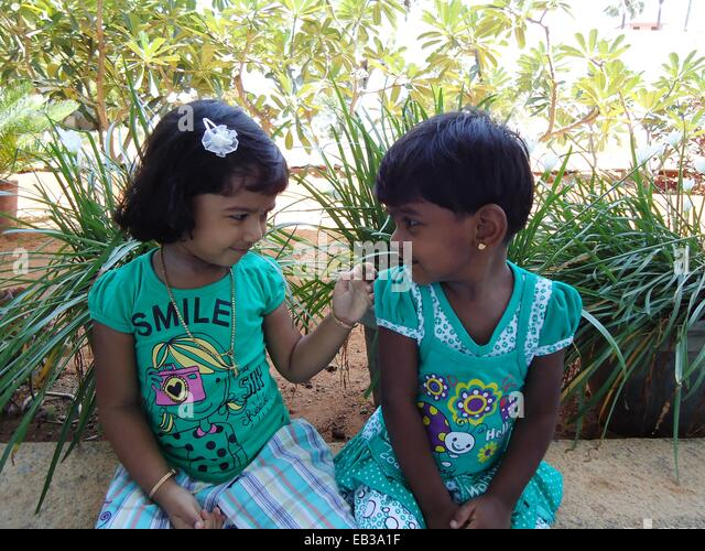 India, Tamil Nadu, Thoothukudi, Kalugumalai, Two girls (2-3) sitting on flowerbed parapet in garden, looking at - Stock Image
