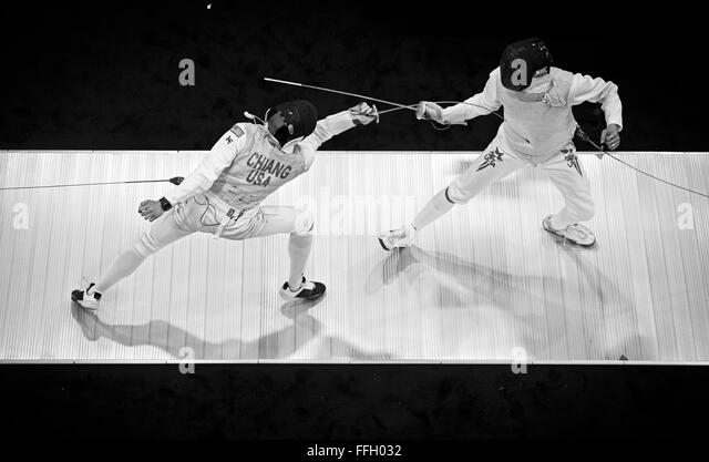 During a foil fencing match, Alexander Chiang reaches out and hits his opponent to score a point. Foil is one of - Stock Image