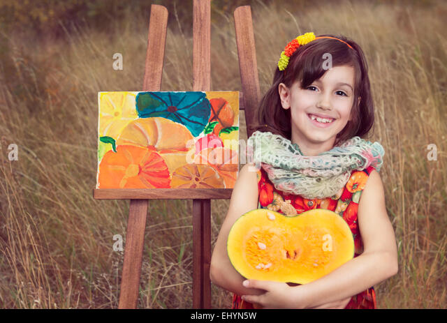 Girl sitting with pumpkin by a painting of pumpkins - Stock Image