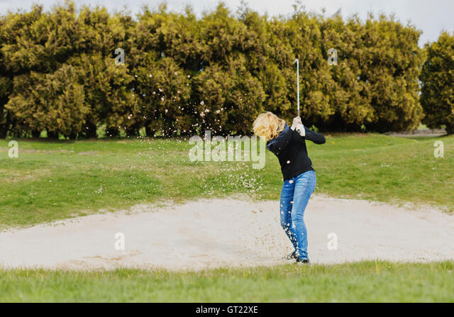 Woman playing golf on field against trees - Stock-Bilder