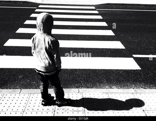 Boy waiting at zebra crossing - Stock Image