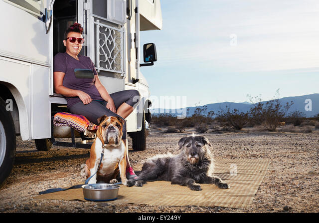 Portrait of mid adult woman and two dogs sitting on camper van step, Borrego Springs, California, USA - Stock-Bilder