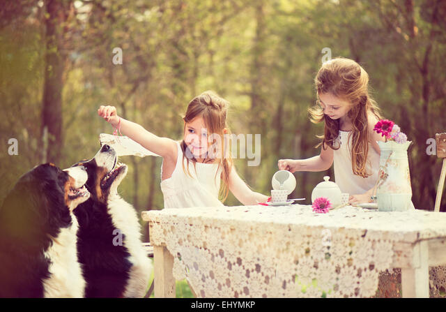 Two girls having a tea party in the garden with two dogs - Stock Image