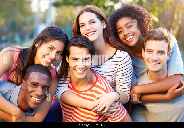 Outdoor Portrait Of Young Friends Having Fun In Park - Stock Image
