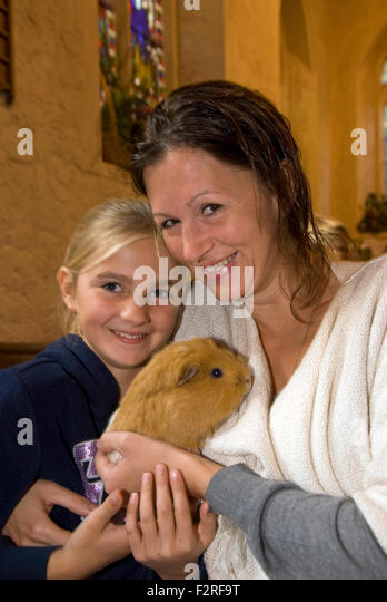 Mother and 10 year old daughter and their guinea pig at a church service where the congregation were invited to - Stock Image