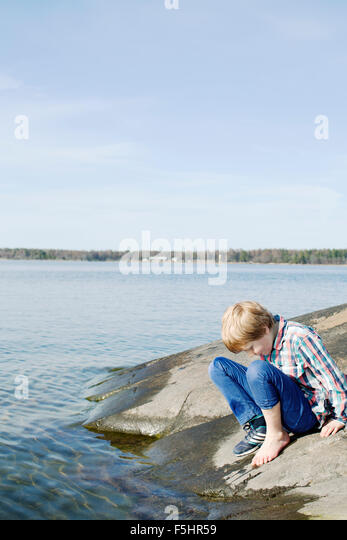 Sweden, Uppland, Oregrund, Boy (8-9) checking temperature of sea water with his foot - Stock Image