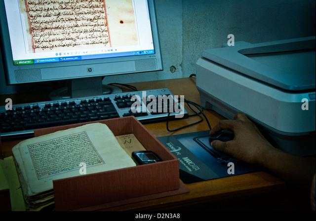 Scanning manuscript at the CEDRAB ( Centre de Documentation et Recherches Historiques Ahmed Baba) .Timbuktu. Mali. - Stock Image