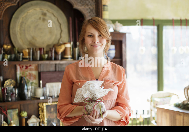 A young woman standing in a store full of antique objects holding a tied packet with ribbon - Stock Image