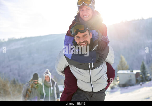 Portrait playful couple piggybacking in sunny, snowy field - Stock-Bilder