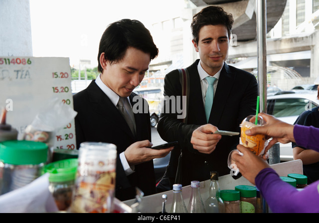 Businessmen buying lunch together at food cart - Stock Image