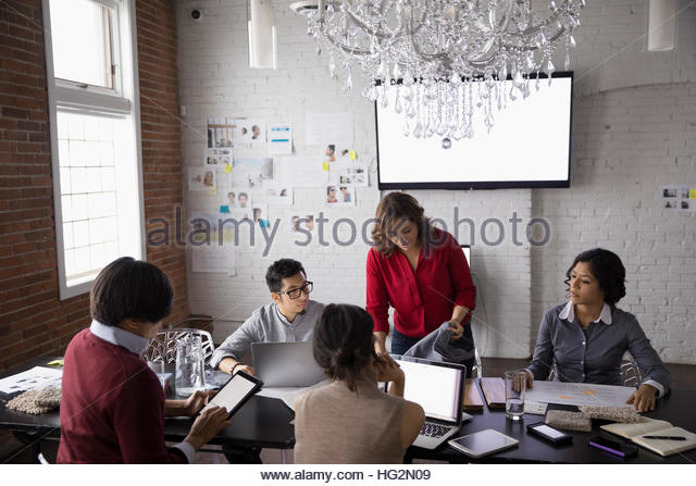 Hispanic designers meeting using laptops in conference room - Stock Image