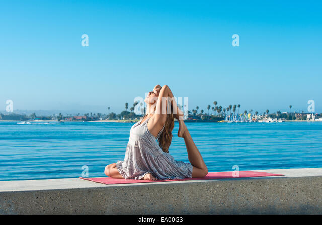 Young woman practicing yoga position on pier at Pacific beach, San Diego, California, USA - Stock-Bilder