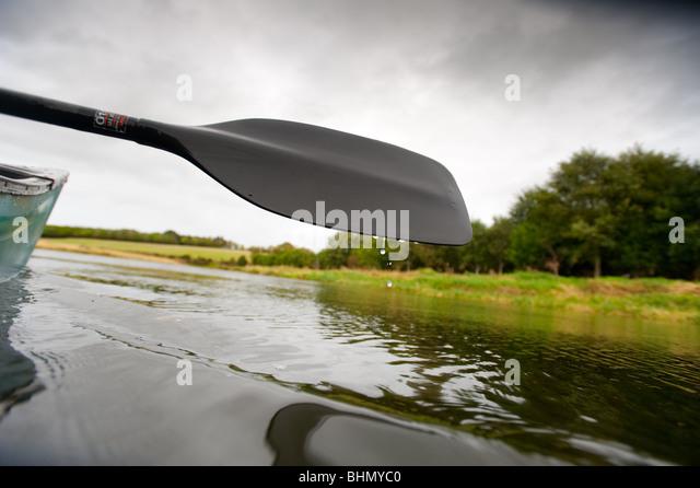 image of water droplets falling off canoe oar - Stock Image