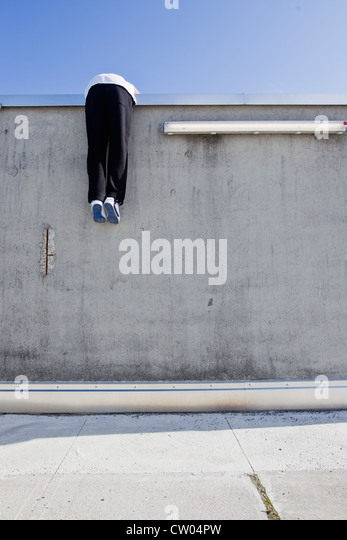 Man scaling wall on city street - Stock-Bilder