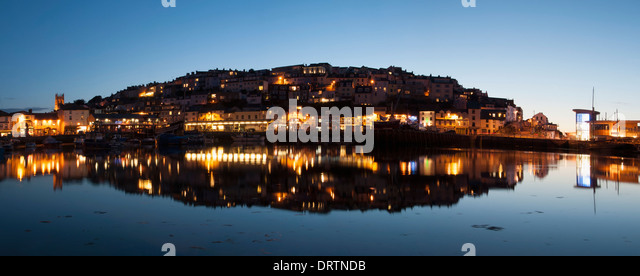 Panoramic of Brixham harbour at early evening with a reflection in the water. - Stock Image