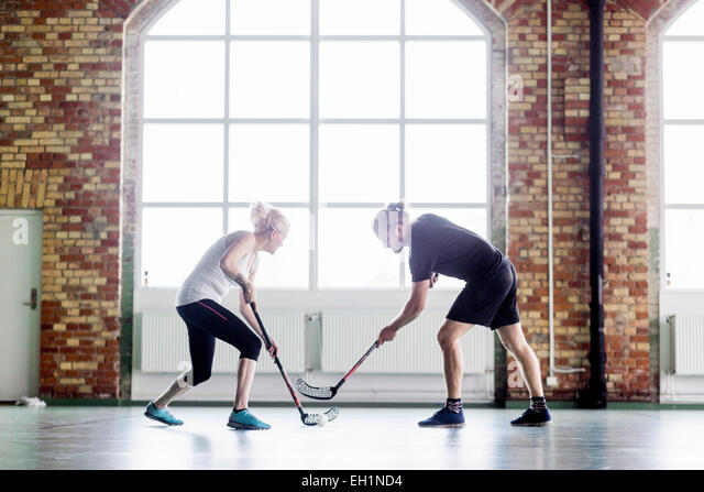 Full length of man and woman playing hockey in health club - Stock Image