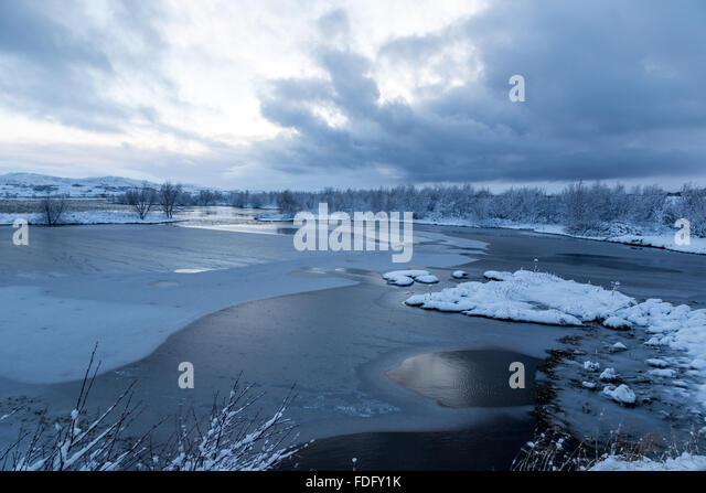 The low winter sun gives dim light to the lakes in the valley near Thingvellir in Iceland. - Stock Image