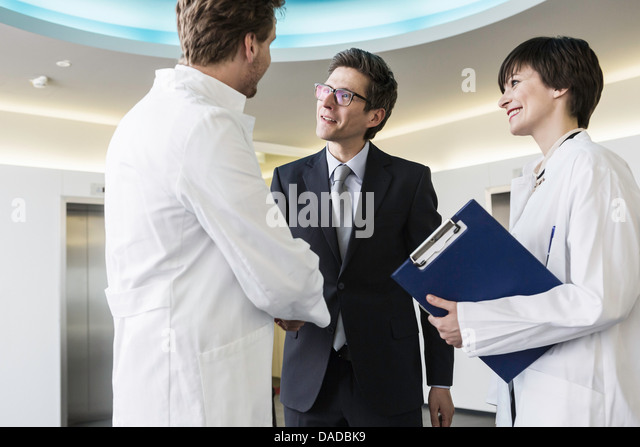 Man wearing lab coat shaking hands with man wearing business attire - Stock Image